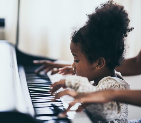 Mother is teaching piano tricks, African people